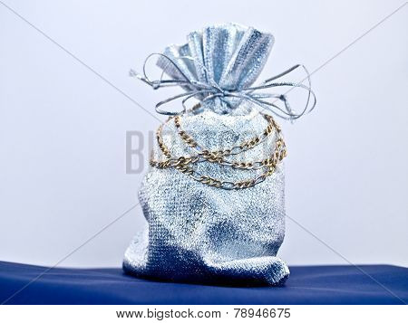 Gold necklace gift against bluish background