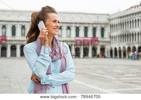 Portrait Of Happy Young Woman Talking Cell Phone On Piazza San Marco In Venice, Italy