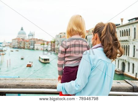Mother And Baby Girl Standing On Bridge With Grand Canal View In Venice, Italy. Rear View