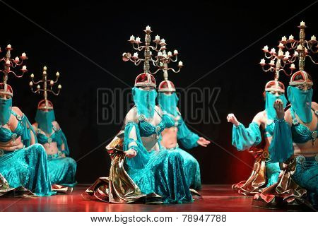 MOSCOW, RUSSIA - APR 26, 2014: Women in green dress dance with beautiful candelabras on heads in art cafe Durov