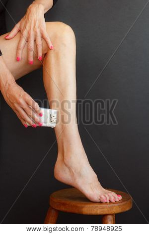 A Woman Shaves Her Legs On The Stool With The Epilator