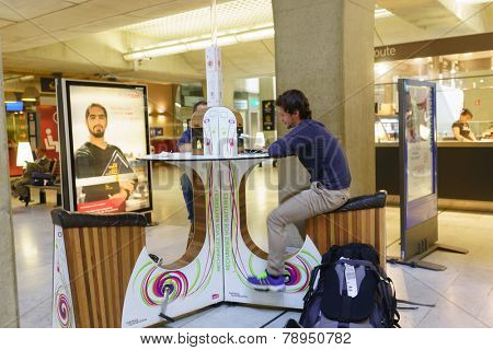 PARIS - SEPTEMBER 10: man charge phone in airport on September 10, 2014 in Paris, France. Paris Charles de Gaulle Airport, is one of the world's principal aviation centres