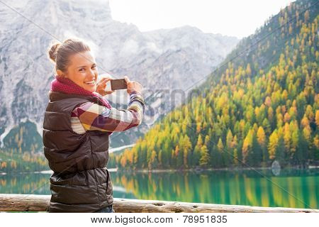 Smiling Young Woman Taking Photo On Lake Braies In South Tyrol,