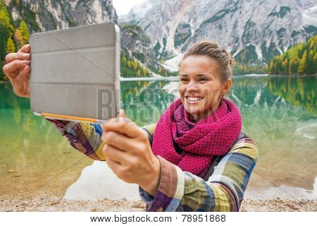 Happy Young Woman Taking Photo With Tablet Pc While On Lake Brai