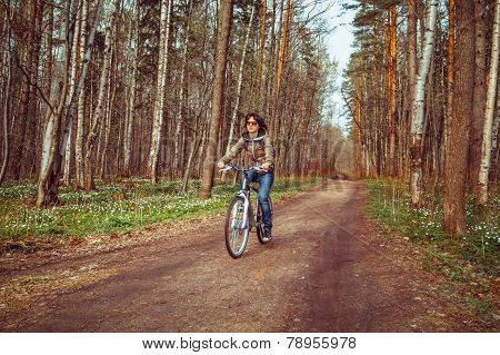 Woman riding on bicycle in a forest