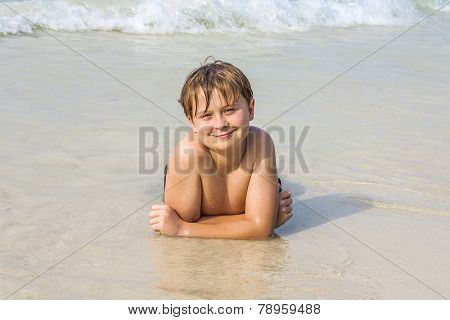 Boy At The Beach Enjoys The Sandy Beach