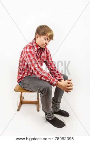 Sad Looking Young Boy With Red Shirt Sitting On A Wooden School  Chair
