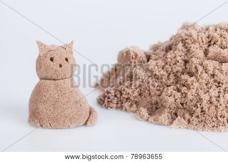 Cat sculpture from wet sand on a white background