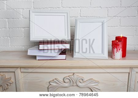 Photo frames with candles on wooden chest of drawers, on brick wall background