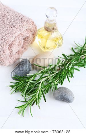 Branches of rosemary, towels and bottle with massage oil on color wooden background. Rosemary spa concept
