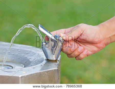 Man's Hand Turns On The Drinking Water Faucet At Public Park.