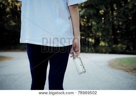 Teen girl standing outside with beer bottle