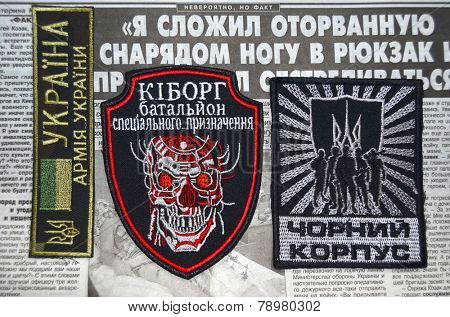 Kiev,Ukraine.Oct 16.Illustrative editorial.Pro-Ukrainian nationalist formation Black Corps chevrone .Newspaper with heroic story of soldier as background.At October 16,2014 in Kiev, Ukraine