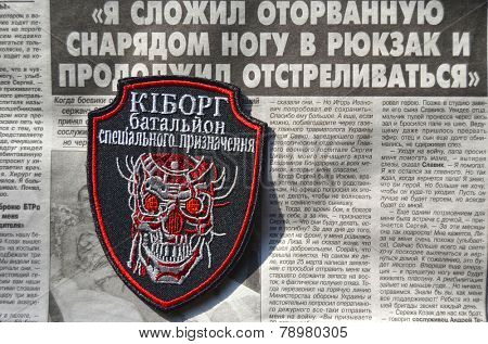 Kiev,Ukraine.Oct 16.Illustrative editorial.Ukrainian Army unformal chevron Kiborg. Newspaper with heroic story of soldier as background.At October 16,2014 in Kiev, Ukraine