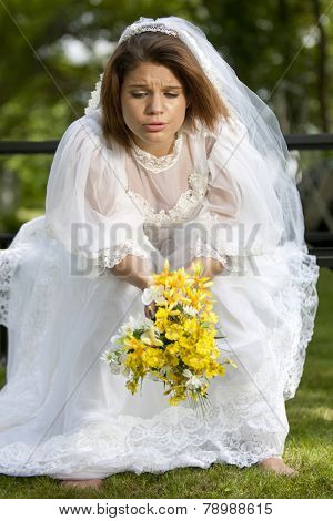 A pretty young summer bride distressed on her wedding day.