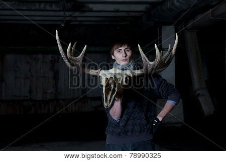 young man with a deer skull with horns