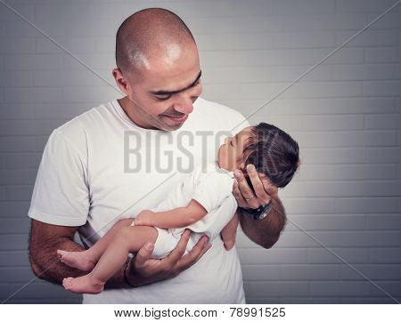 Portrait of handsome father holding on hands cute little baby, spending time at home, lovely young family, love and happiness concept