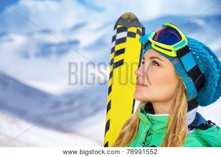 Closeup portrait of beautiful skier girl wearing mask and holding ski, enjoying winter holidays in Europe