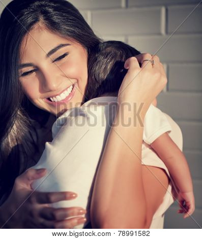 Closeup portrait of cute smiling mother holding on hands little baby, having fun at home, happy parenthood, family love concept