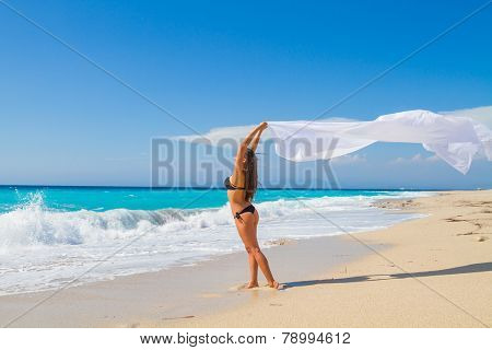 Beautiful Girl With White fabric on The Beach. Travel and Vacation. Freedom Concept.