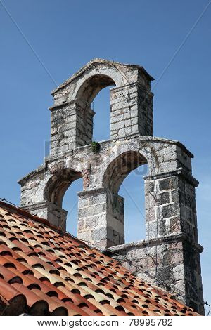 BUDVA, MONTENEGRO - JUNE 09, 2012: The bell tower of the church of Saint Mary in Punta, Budva, Montenegro, on June 09, 2012