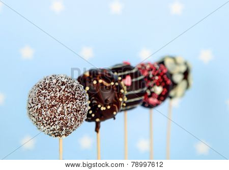 Tasty cake pops on blue background