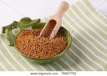 Mustard seeds in bowl on  wooden background