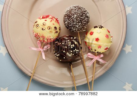 Tasty cake pops on plate, close up