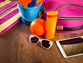 stock photo of leaving  - Leaving for vacations on the beach with digital tablet and colorful luggage and accessories - JPG