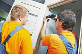 picture of carpenter  - Two male workers carpenters at internal door installation - JPG