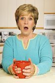 Senior Woman, Holding A Coffee Mug In Her Kitchen, With A Look Of Shock On Her Face.
