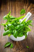 pic of crusher  - Fresh basil in a mortar on a wooden table - JPG