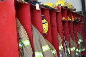 foto of firehouse  - A line of coats and hats in a firehouse - JPG