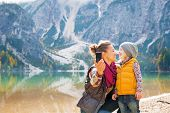 stock photo of mother baby nature  - Happy mother and baby making selfie on lake braies in south tyrol italy - JPG