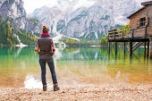 picture of south tyrol  - Full length portrait of young woman on lake braies in south tyrol italy - JPG