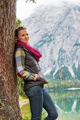 stock photo of south tyrol  - Young woman standing near tree on lake braies in south tyrol italy - JPG