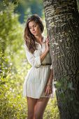 foto of daydreaming  - Attractive young woman in white short dress posing near a tree in a sunny summer day - JPG