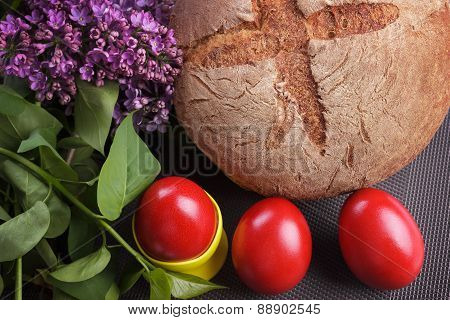 Traditional Easter red eggs with bread and lilac