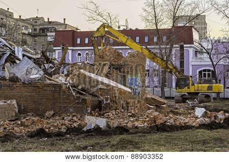Excavator And Ruins Of The Old Brick Building