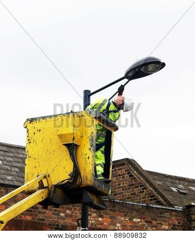 Worker paints a street lamp