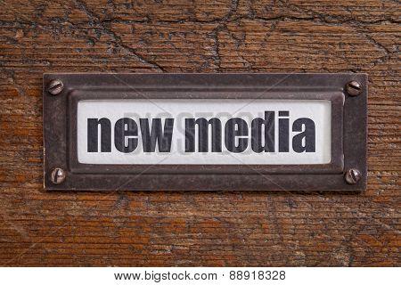 new media - file cabinet label, bronze holder against grunge and scratched wood