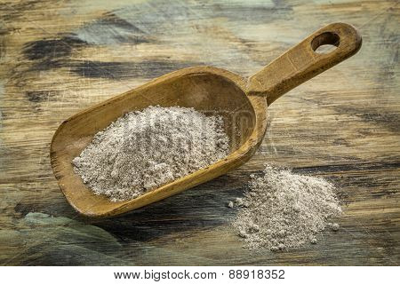 scoop and heap of gluten free buckwheat flour against painted wooden cutting board