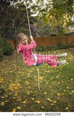 Cute girl playing on a backyard rope swing outdoors