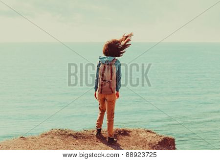 Woman Standing On Coastline In Windy Weather