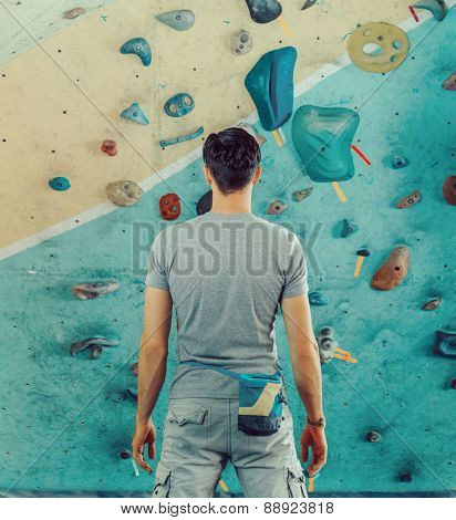 Man Standing In Front Of A Climbing Wall