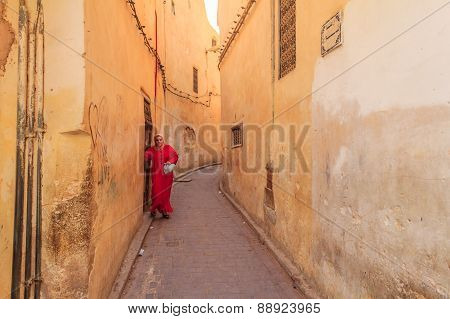 Woman Walking Out Into A Narrow Street In The Medina