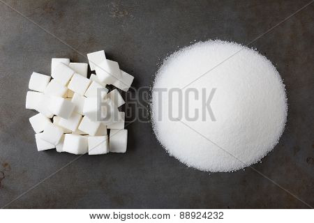 Overhead view of a pile of granulated white sugar and a mound of sugar cubes, on a used baking sheet.
