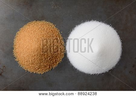 A pile of white granulated sugar and one of raw turbinado granules on a baking sheet.