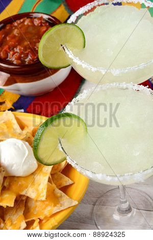 High angle view of two margarita cocktails for a Cinco de Mayo celebration. Surrounded by nacho chips and salsa on a bright Mexican table cloth.