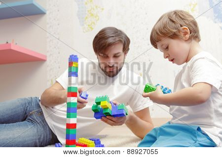 Father and son play with building kit
